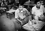 Young men sip tea in sidewalk cafe in central Yangon, Burma.