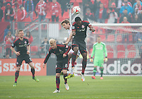 Toronto, Ontario - May 3, 2014: Toronto FC defender Doneil Henry #15 and Toronto FC midfielder Kyle Bekker #8 battle for a ball with New England Revolution forward Patrick Mullins #7 during a game between the New England Revolution and Toronto FC at BMO Field.<br /> The New England Revolution won 2-1.