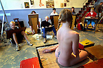 A nude model sits in a relaxed posed for artists during a studio class.