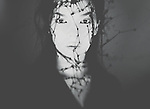 Dark closeup of woman staring, with ink dripping around her face