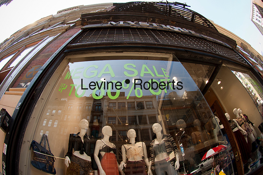 A clothing store in the Soho neighborhood in New York advertises its sales on Friday, September 14, 2012.  (© Frances M. Roberts)