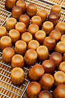 Freshly-baked French Bordeaux speciality canele cakes on sale at food market in Bordeaux region of France