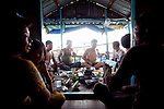 Neighbors gather for lunch on their boat house on the Hau Giang River, a tributary of the Mekong River, in Chau Doc, in the An Giang Province, Vietnam. Most of the family members are fishermen and have lived on the river for most of their lives. When the Mekong River reaches Vietnam it splits into two smaller riveres. The &quot;Tien Giang&quot;, which means &quot;upper river&quot; and the &quot;Hau Giang&quot;, which means &quot;lower river&quot;. Photo taken on Monday, December 7, 2009. Kevin German / Luceo Images
