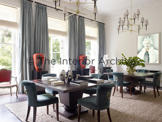 The dining room is furnished with a pair of square tables and custom-made velvet-upholstered chairs overseen by a holographic portrait of Queen Elizabeth II by Chris Levine