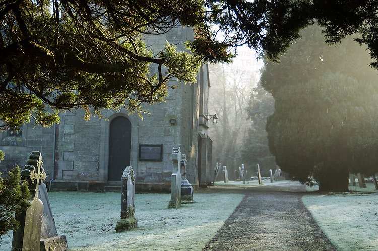 English graveyard during winter with church and gravestones