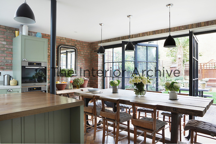 Floor-to-ceiling patio doors open out into Kally Ellis's walled garden from her rustic kitchen/dining room