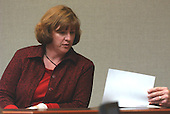 Spotsylvania County  (Virginia) sniper victim, Caroline Seawell, looks at a photograph of her wounds during her testimony in the trial of sniper suspect John Allen Muhammad in courtroom 10 at the Virginia Beach Circuit Court in Virginia Beach, Virginia on October 28, 2003. <br /> Credit: Adrin Snider - Pool via CNP