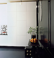 Graphic patterns, added to a simple palette of black and white creates an elegant combination. In the kitchen a simple table and stool are set to one side. A run of flush cupboards provides plenty of storage