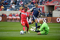 Chicago forward Patrick Nyarko (14) dribbles past New England goalkeeper Matt Reis (1).  The Chicago Fire defeated the New England Revolution 3-2 at Toyota Park in Bridgeview, IL on Sept. 25, 2011.