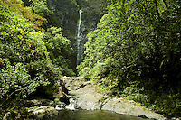 Young man hiking up to Hanakapiai Waterfall in Kauai's Na Pali coast