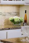 Detail shot of neutral-colored tile backsplash and granite countertops