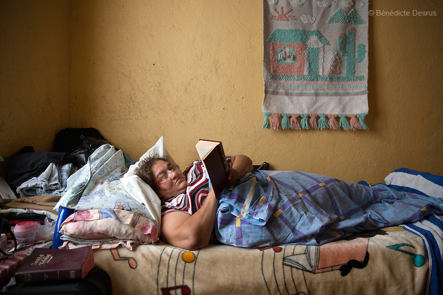 Maria Isabel, a resident of Casa Xochiquetzal, reads a book in her bed at the shelter in Mexico City, Mexico on September 3, 2013. Casa Xochiquetzal is a shelter for elderly sex workers in Mexico City. It gives the women refuge, food, health services, a space to learn about their human rights and courses to help them rediscover their self-confidence and deal with traumatic aspects of their lives. Casa Xochiquetzal provides a space to age with dignity for a group of vulnerable women who are often invisible to society at large. It is the only such shelter existing in Latin America. Photo by Bénédicte Desrus