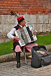 A man playing an accordion and dress in traditional clothes, outside of Wawel Castle in Krakow, Poland