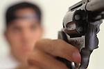 Teen (17 years old) boy pointing loaded handgun.