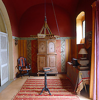 In this entrance hall the deep terracotta colour of the vaulted ceiling focuses attention on the multicoloured patterned wall below