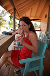 Belize, Central America - Woman in red dress sucks on  tropical drink in Placencia.