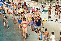 Spain. Mallorca in the Balearic islands. Colonia Sant Jordi. Men , women and children, all tourists, walk on the sandy beach. Mediterranean sea.  © 1999 Didier Ruef