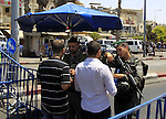 Israeli police officers chek the IDs of Muslim Palestinians as others take part in Friday noon prayers in the east Jerusalem neighbourhood of Ras al-Amud on July 31, 2015, following restrictions by Israeli police to allow entry to men only above 50-year-old wanting to access the Al-Aqsa Mosque compound. Photo by Saeb Awad