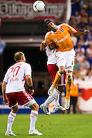 Calen Carr (3) of the Houston Dynamo goes up for a header as Joel Lindpere (20) of the New York Red Bulls watches. The New York Red Bulls defeated the Houston Dynamo 2-0 during a Major League Soccer (MLS) match at Red Bull Arena in Harrison, NJ, on August 10, 2012.