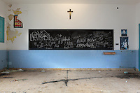 A room with a blackboard in an abandoned building in a state of dereliction, possibly a school, with a crucifix on the wall, in the old town or Casc Antic of Tortosa, Tarragona, Spain. Tortosa is an ancient town situated on the Ebro Delta which has a rich heritage dating from Roman times. In recent years, many buildings in the old town have been abandoned and fallen into disrepair. Picture by Manuel Cohen