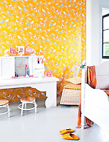 Golden wallpaper depicting birds and butterflies covers one wall of Zara's white bedroom
