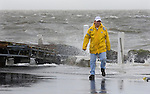 A Cedar Key, Florida resident walks back to his vehicle after checking out a dock the had washed up on shore, behind left, as the storm surge arrived from Tropical Storm Alberto June13, 2006. REUTERS/Scott Audette