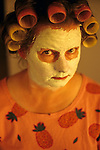 Woman, mother at dining room table with facial mask and hair in curlers looking into camera, Marysville, Washington USA   MR.