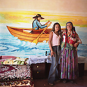 Nadia stands with her grandmother, Sibinca, in front of a hand painted mural depicting a pilgrim father, in the one of the bedrooms of their home, in  the Roma camp of Sintesti.