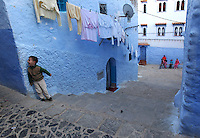 "A little boy laughs at something at the top of one of the many stairways in Chefchaouen, Morocco, whose ""medina"" (old city) is famous for its striking blue walls."