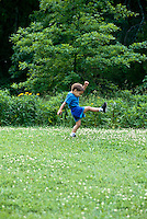 Boy practices his kick with enthusiasm in a summer lawn