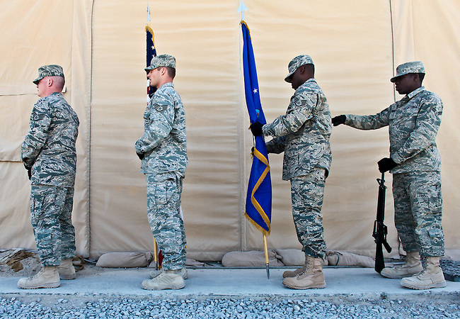 A member of an Air Force color guard makes a last-minute adjustment to a fellow airman's uniform before a Memorial Day ceremony at Kanadahar Airfield, Afghanistan. May 31, 2010. DREW BROWN/STARS AND STRIPES