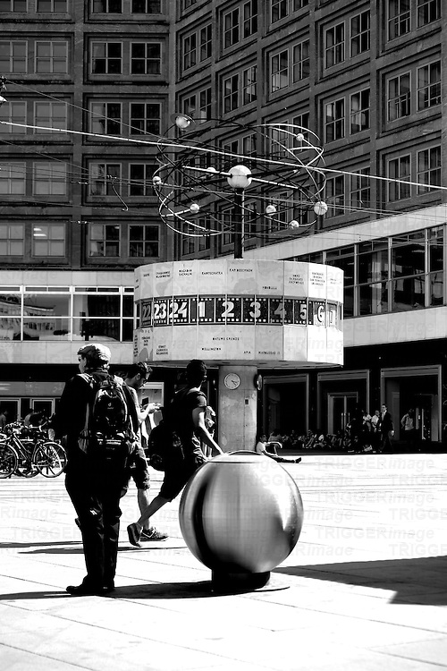 Passersby stroll in good weather all around the world clock on the Alexander Place in Berlin.