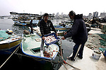 Palestinian fishermen work on their boats in the port of Gaza City on March 31, 2013. An Israeli military spokesman announced on March 21, that the Israeli military will again reduce the permitted fishing range in the Gaza Strip from six nautical miles to three (approximately 5.5 kilometres), in response to missile fire by armed Palestinian groups towards the south of Israel earlier that morning. Photo by Emad Nassar