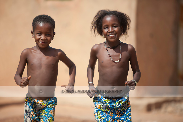 Two Fulani children run towards the camera in Djibo in northern Burkina Faso.