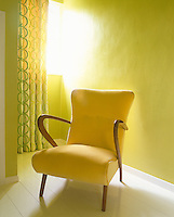 Retro armchair upholstered in buttercup yellow against an acid yellow wall