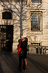 A mature romantic couple kiss and cuddle in a London street.