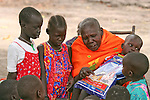 In Rumbek, South Sudan, a grandmother speaks to the children about preventing malaria by sleeping under long lasting insecticide-treated mosquito nets, such as Serena, distributed by the international NGO, Population Services International (PSI).