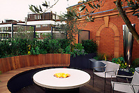Wide angle view of tiny roof terrace with arching wooden bench, flambe' chairs and water feature
