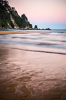 Pastel colours of twilight on golden beach in Totaranui, Abel Tasman National Park, Nelson Region, New Zealand