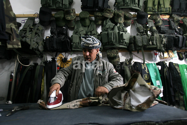 A Palestinian tailor irons a military uniform at his workshop in the southern of Gaza strip town of Rafah on March 19, 2013. Egyptian forces seized military-style clothing from a smuggling tunnel near the Gaza border, an Egyptian army spokesman said Sunday, which was denied by Palestinian officials said that the smuggling fabric using to sew Palestinian military uniforms which almost resemble the Egyptian military uniforms and used by the Palestinian police and the military wings of Palestinian parties. Photo by Eyad Al Baba