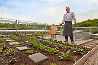 Chef Brad Long waters his rooftop kitchen garden at the Evergreen Brick Works, home of the new Belong Caf&eacute;.