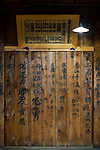 """Photo shows the exterior wall of the """"gakuya"""" dressing room area of Korakukan theater, Japan's oldest extant wooden playhouse in Kosaka, Akita Prefecture Japan on 19 Dec. 2012. On the walls is the graffiti -- written by actors -- for which the theater is also famed. Above the graffiti hangs an old """"hengaku"""" (literally """"picture frame"""") which served as theater programs in the days before paper became more widely available. Photographer: Robert Gilhooly"""
