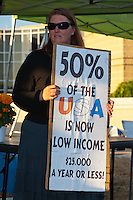 "A woman holds a sign reading ""50% of hte USA is now low income $25,000 a year or less"" while standing at the Occupy Orange County - Irvine camp.  The background is the Irvine Civic Center building near sunset."