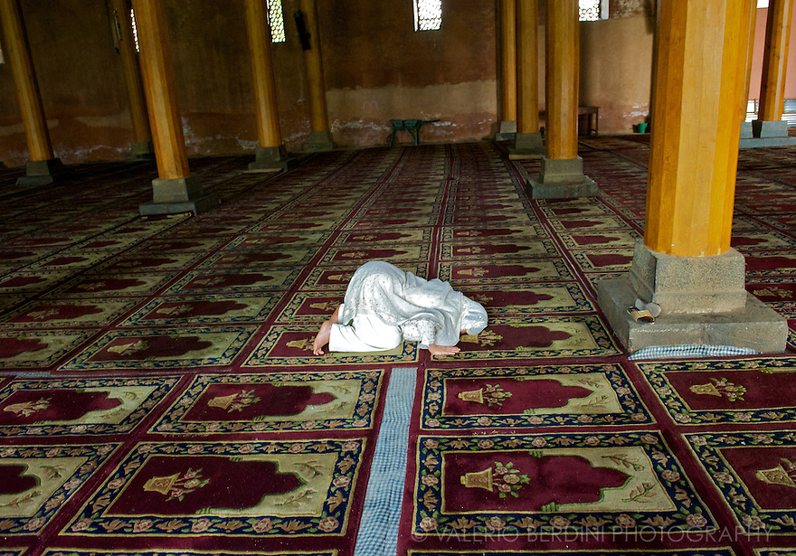 A solitary woman praying facing Mecca in the Jamia Masjid.