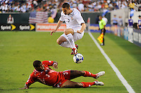 Heath Pearce (2) of the United States (USA) jumps over the tackle by Luis Moreno (3) of Panama (PAN). The United States (USA) defeated Panama (PAN) 2-1 during a quarterfinal match of the CONCACAF Gold Cup at Lincoln Financial Field in Philadelphia, PA, on July 18, 2009.