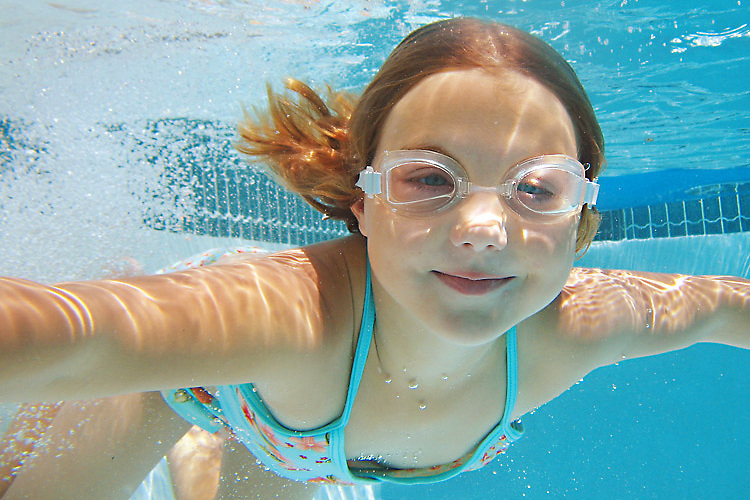 A girl smiles for the camera as she swims underwater in a pool.