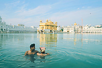 Two young men bathe in the Sarovar, the sacred waters surrounding the Golden Temple in Amritsar, Punjab, India.<br />