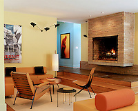 A sofa and armchairs are arranged around occasional tables in a sunken living area below a stone-clad fireplace