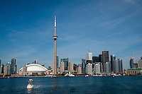 Toronto Skyline from the Hanlan Point/Toronto Islands Ferry. The islands are a popular park just a ten minute ferry ride into Lake Erie off the Toronto waterfront. The view includes the CN Tower, the tallest freestanding structure in the western hemisphere. The iconic communications and observation tower rises to 1,815 feet/553 meters snd was completed in 1976. The tower is among the modern Seven Wonders of the World compiled by the American Society of Civil Engineers. The Toronto Blue Jays Rogers Center baseball stadium sits to teh left of the tower.