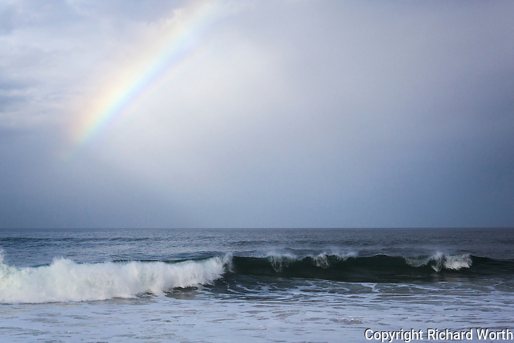 A slice of rainbow glows above a gentle wave along California's coast.